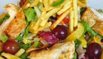 Maaltijdsalade met pittige kip, druiven en knapperige aardappelsticks
