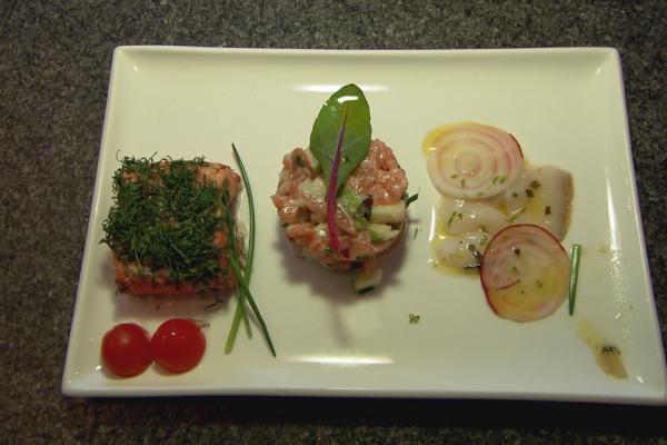 Trio van vis: coquilles, zalm op een cederplankje en tartaar van zalm ...
