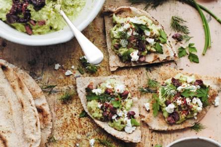 Platbrood en avocadopuree met tahin en olijven
