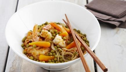 Wok van scampi's met noedels, erwtjes, worteltjes en kruiden ...