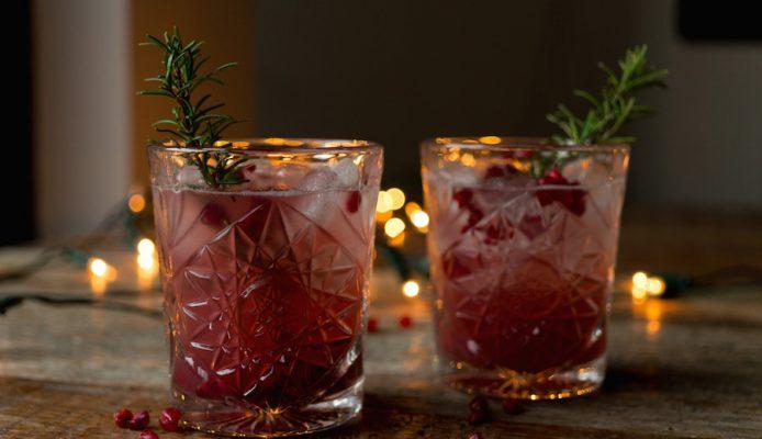 Kerstcocktail van gin met rozemarijn en granaatappel