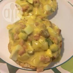 Gebakken stukjes ei met groenten en ham in een romige saus ...